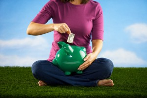 Woman Putting Dollar Bill in to Piggy Bank